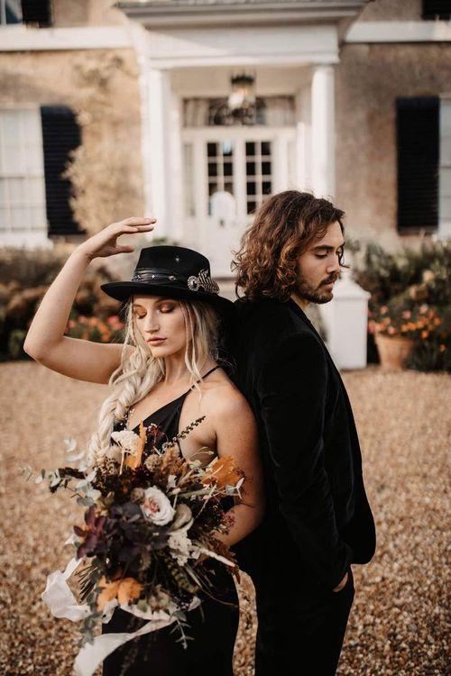 Halloween wedding with bride in black dress and hat and groom in  velvet jacket
