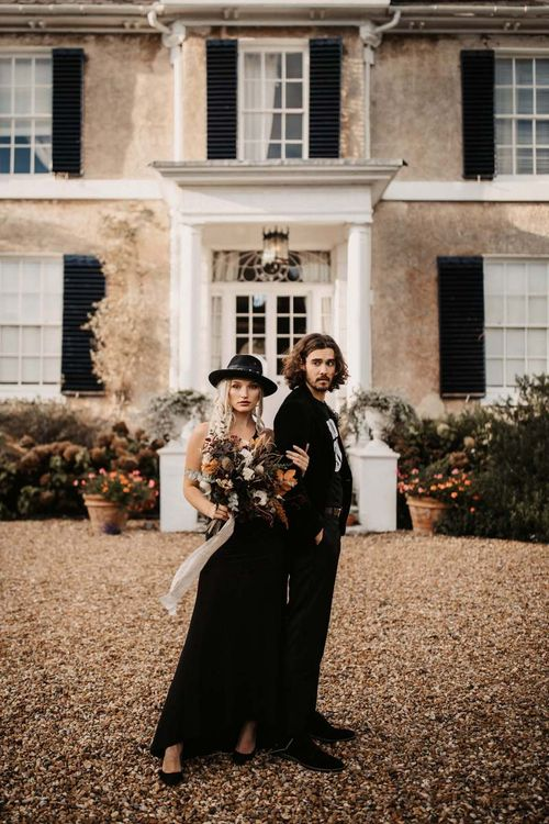 Stylish bride and groom in black wedding dress and hat for Halloween wedding  shoot