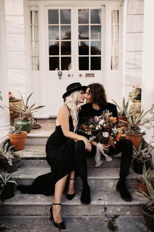Groom in black velvet blazer holding a autumn wedding bouquet at Preston Court