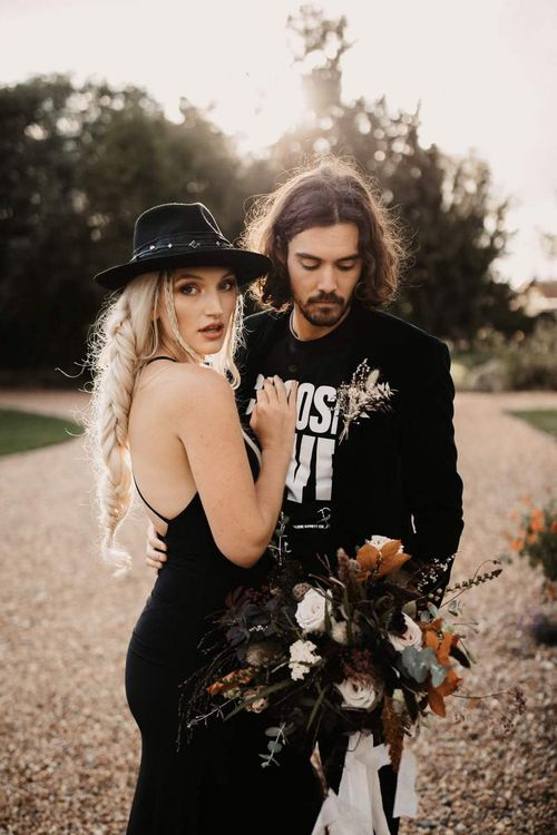 Cool bride and groom in black wedding dress, hat T-shirt and blazer for Halloween wedding  shoot