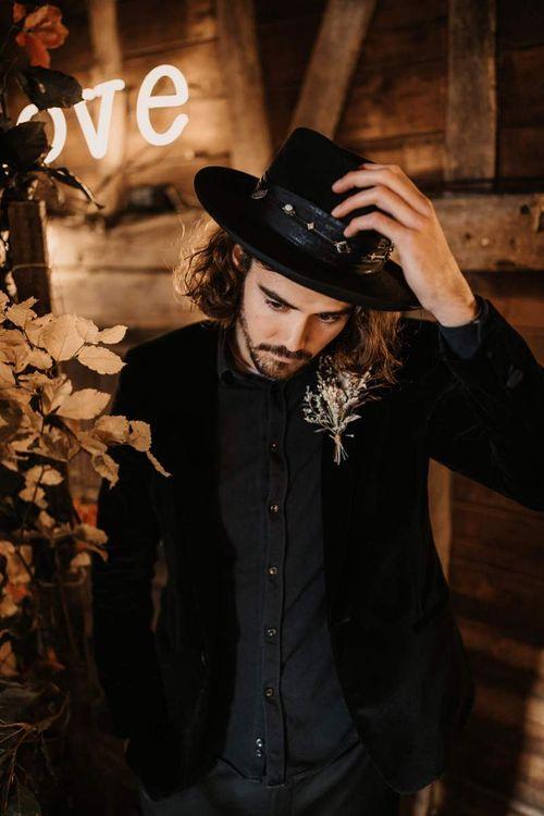 Groom in black shirt, hat and blazer at Halloween wedding