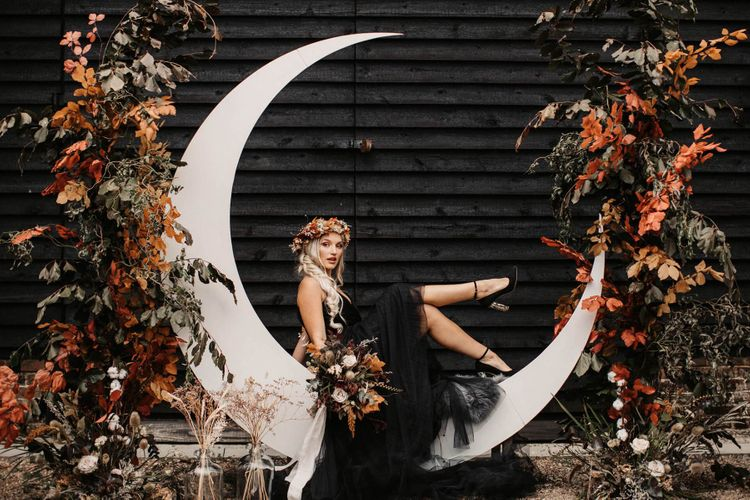 Stylish bride in black wedding dress sitting on a crescent moon  at Halloween wedding