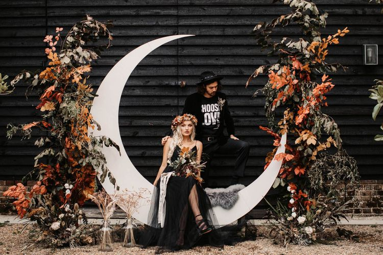 Stylish bride and groom sitting on a crescent moon flanked by autumnal floral arrangements  at Halloween wedding