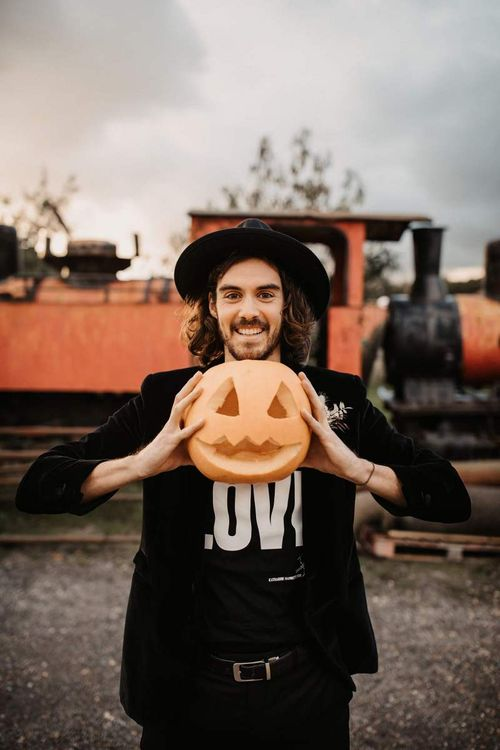 Groom in t-shirt, blazer and hat holding at carved pumpkin at Halloween wedding