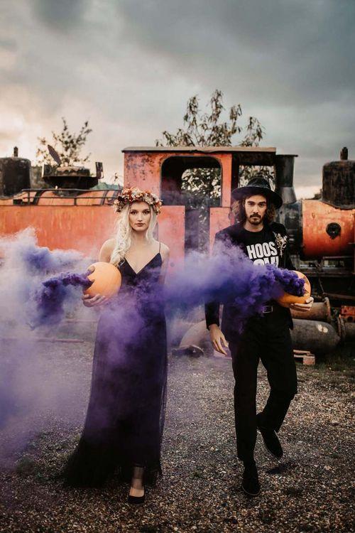 Stylish bride and groom with purple smoke bombs at Halloween wedding