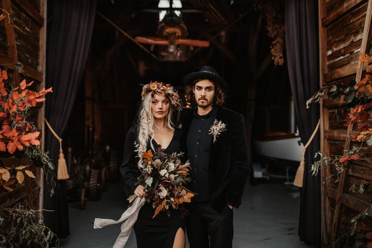 Halloween wedding inspired shoot with bride and groom in black outfits holding Autumn flowers