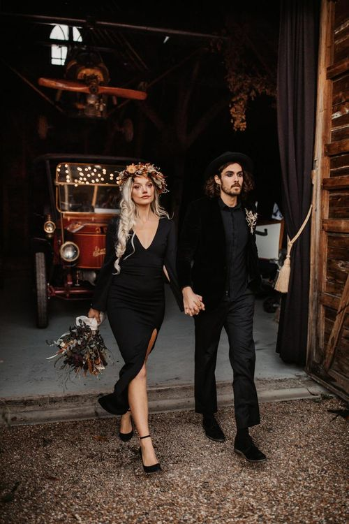 Bride in black dress with side braid and flower crown holding her grooms hand in a black shirt and hat for Halloween wedding