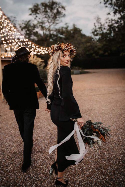 Stylish bride in black wedding dress and orange flower crown