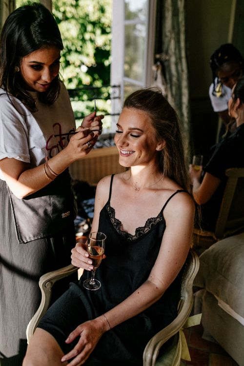 Wedding Morning Bridal Party Preparations with Bridesmaid in Black Slip Having Her Makeup Done