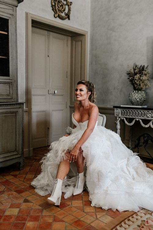 Bride in Stephanie Allin Ostrich Feather Wedding Dress Putting On Her Wedding Boots