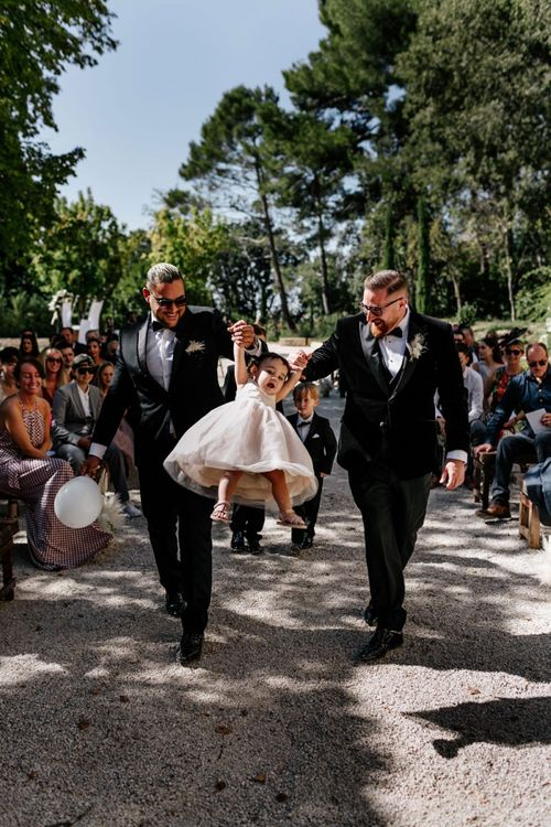 Groom and Best Man Walking Down the Aisle with the Flower Girl