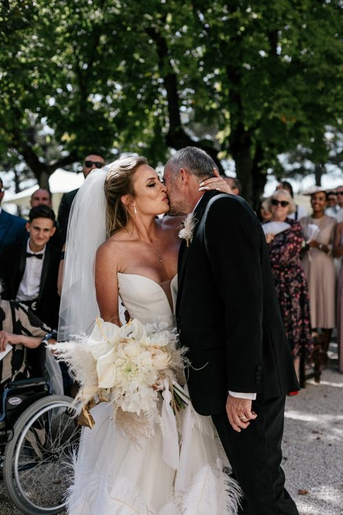 Bride in a Wedding Dress with Feathers Kissing Her Dad at the Altar