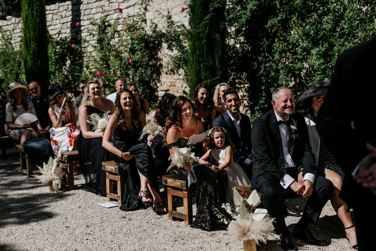 Guests Sitting on Benches at an Outdoor Wedding Ceremony