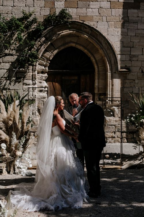 Bride in Feather Wedding Dress and Groom in a Tuxedo Exchanging Vows at the Altar