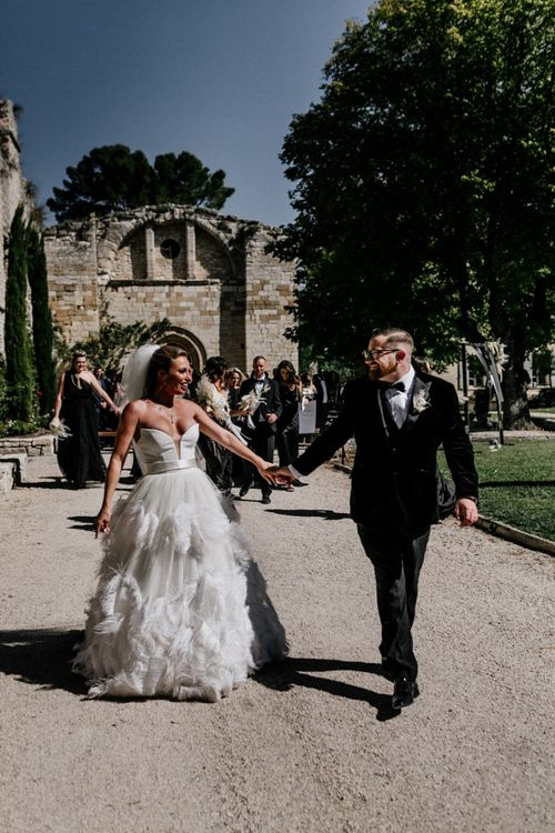 Bride in Stephanie Allin Wedding Dress and Groom in Tuxedo Holding Hands