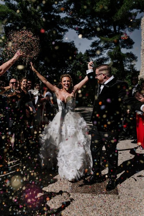 Confetti Moment with Bride in Off the Shoulder Wedding Dress and Groom in Moss Bros. Suit
