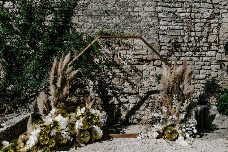 Gold Hexagon Backdrop with Neon Sign, Glitter Balls and Pampas Grass