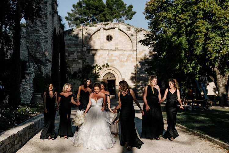 Stylish Bridal Party with Bridesmaids in Black Dresses and Bride in Feather Skirt Wedding Dress