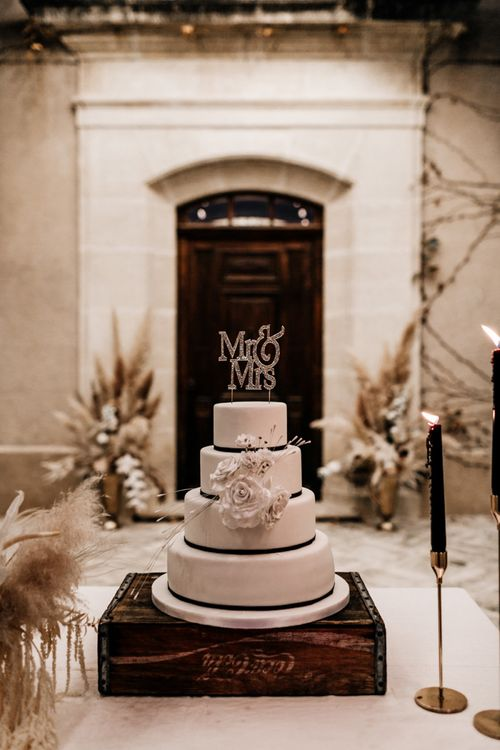 White Iced Wedding Cake with Black Ribbon and Glitter Cake Topper Resting in a Wooden Crate
