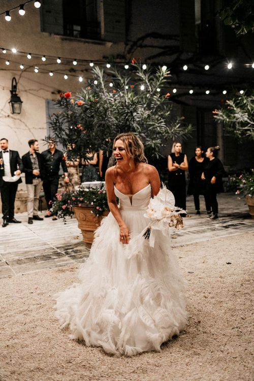 Happy Bride in Off the Shoulder Bodice and Feather Skirt About to Toss Her Wedding Bouquet