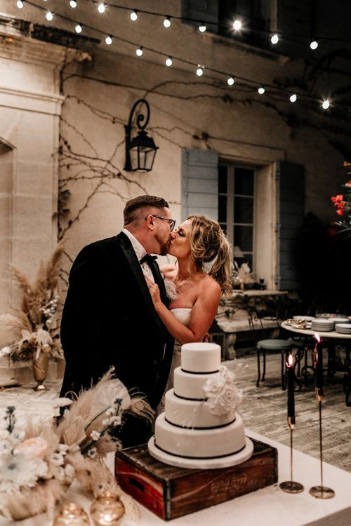 Bride and Groom Kissing After they Cut The Wedding Cake
