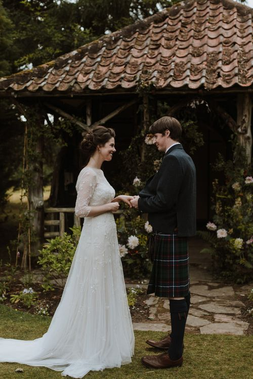 Bride in Embroidery and Floral Embellished Wedding Dress and Groom in Tartan Kilt Exchanging Vows at Outdoor Wedding Ceremony