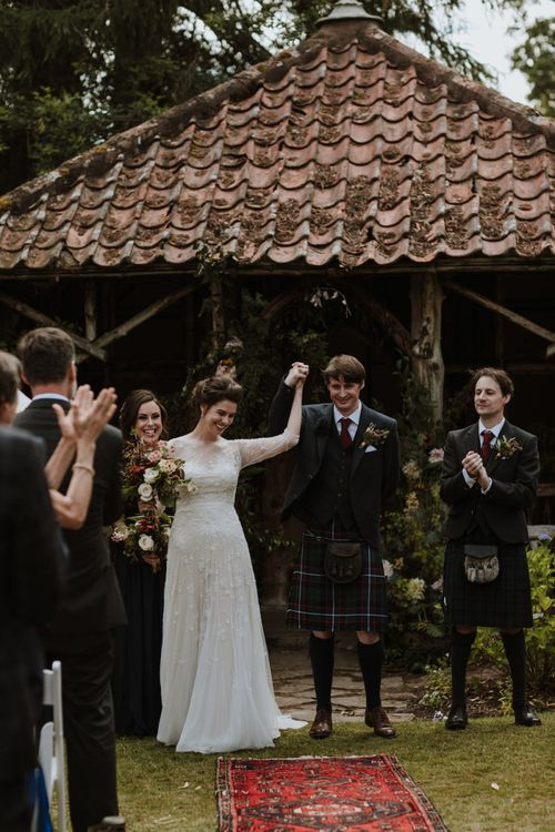 Bride in Embroidery and Floral Embellished Wedding Dress and Groom in Tartan Kilt Just Married