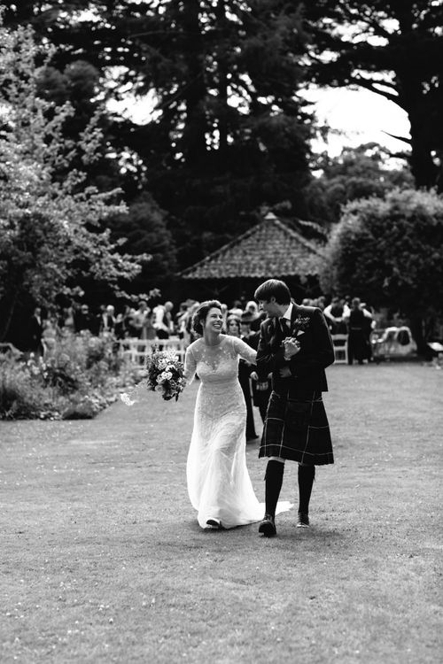 Bride in Embroidery and Floral Embellished Wedding Dress and Groom in Tartan Kilt Laughing