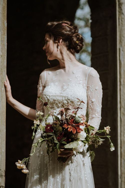 Bride in Wendy Makin French Collection Yvonne Wedding Dress with Embroidery and Floral Embellishments Holding an Autumnal Wedding Bouquet