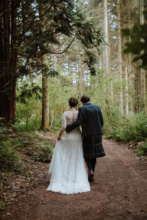 Bride in Wendy Making French Collection Yvonne Wedding Dress with Embrodiery and Floral Embellishments and Groom in Tarn Kilt Walking Through Woodland