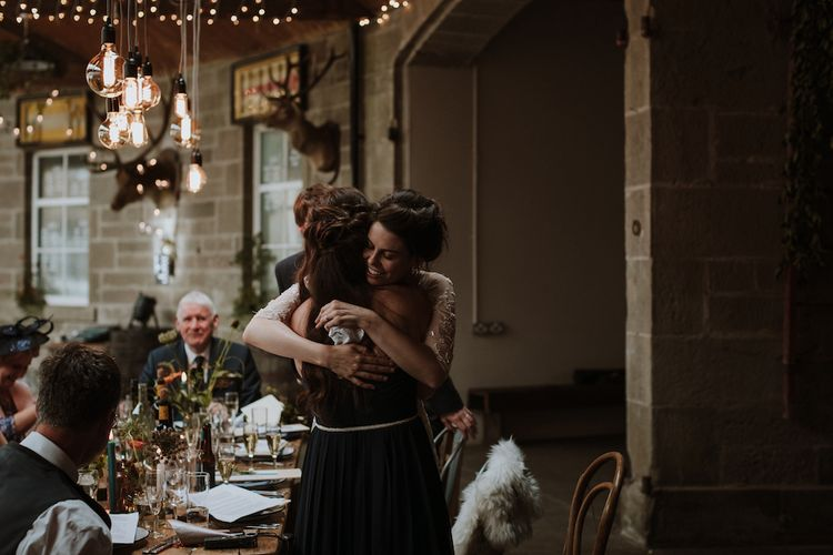 Bride and Bridesmaid Hugging at The Top Table  Illuminated by an Edison Light Installation