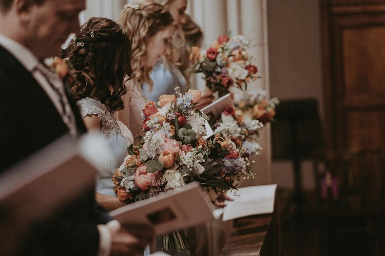 Bridesmaids Holding Order of Service and Colourful Spring Bouquets at Church Wedding Ceremony