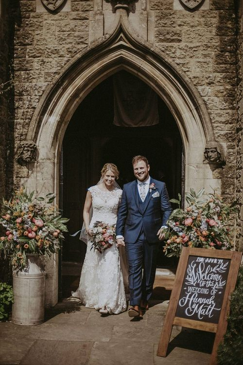 Bride and Groom Exiting the Church with Flower Filled Milk Churns and Chalkboard Wedding Welcome Sign