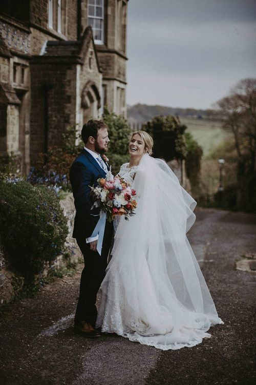 Bride in Everly Maggie Sottero Wedding Dress and Groom in Navy Suit