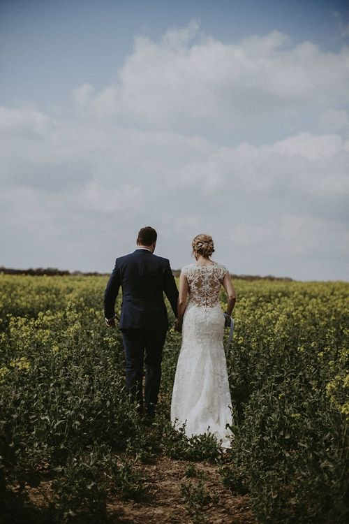 Bride in Lace Back Maggie Sottero Wedding Dress and Groom in Navy Suit Walking Through Fields