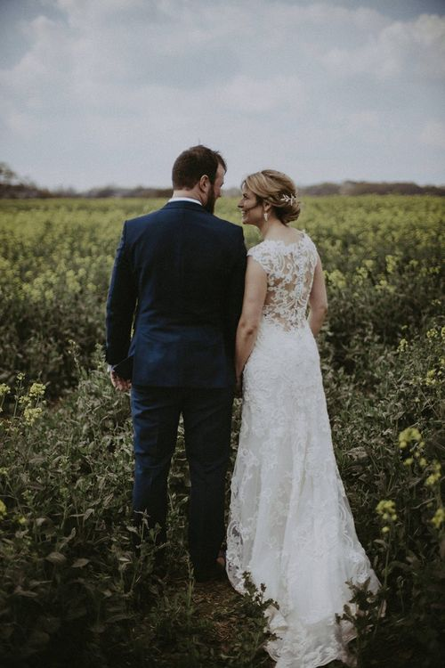 Bride in Lace Back Maggie Sottero Wedding Dress and Groom in Navy Suit Holding Hands in a Field