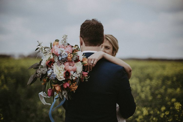 Bride Hugging Groom Whilst Holding a Colourful Spring Bouquet including Pink Peonies