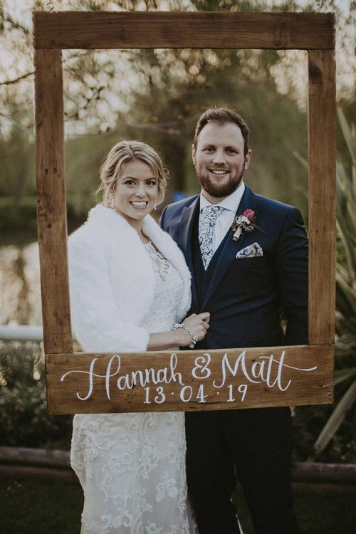 Bride in Faux Fur Stole and Lace Wedding Dress and Groom in Navy Suit Holding a Photo Booth Prop