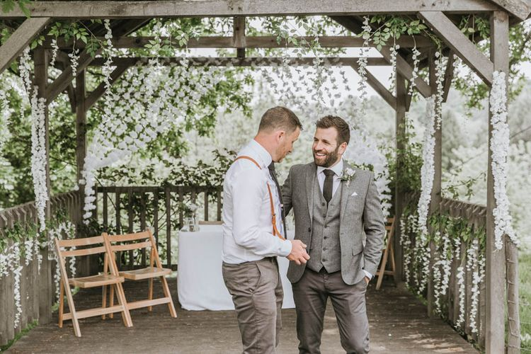 Groom in Three-piece Wool Suit and Best Man in Chino's  and Braces Talking at the Altar