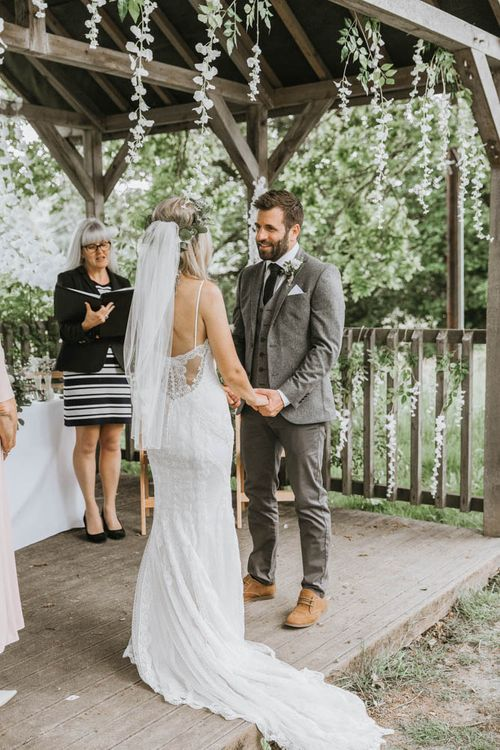 Bride in Lace Wedding Dress and Groom in Wool Suit Exchanging Vows During Outdoor Wedding Ceremony