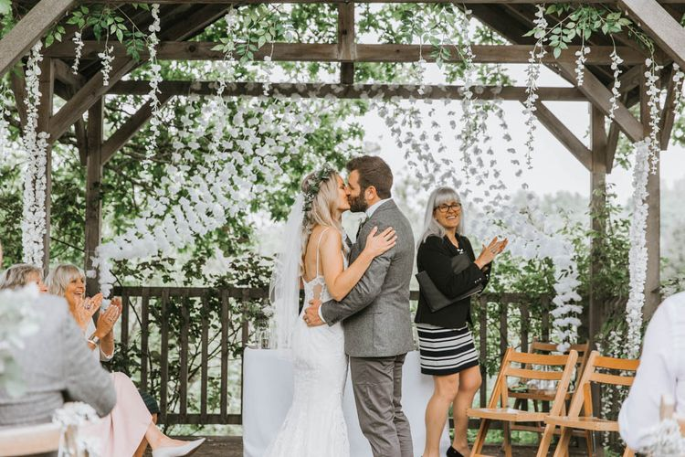 Bride in Lace Wedding Dress and Groom in Wool Suit Kissing During Wedding Ceremony