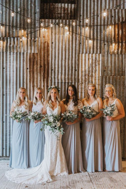 Bridal Party Portrait Under Festoon Lights with Bride in Lace Wedding Dress and Flower Crown and Bridesmaids in Separates