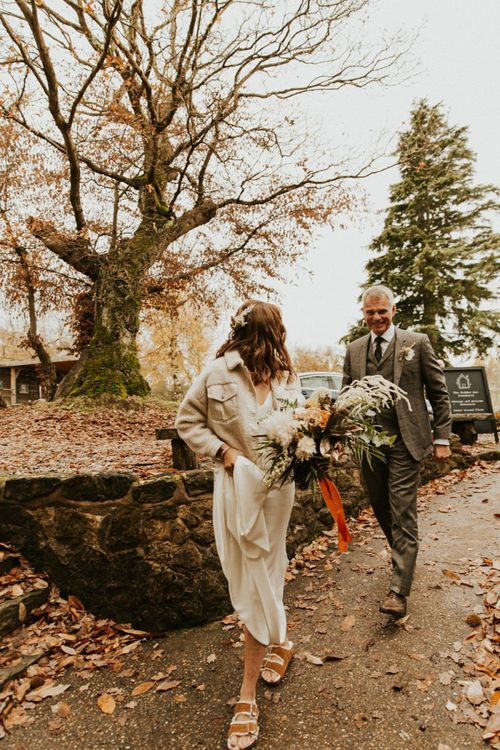 Bride in jacket and Birkentstock shoes on her way to wedding ceremony in Kent
