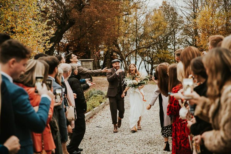 Confetti exit fir bride and groom with bridesmaids wearing bridesmaid jumpsuit