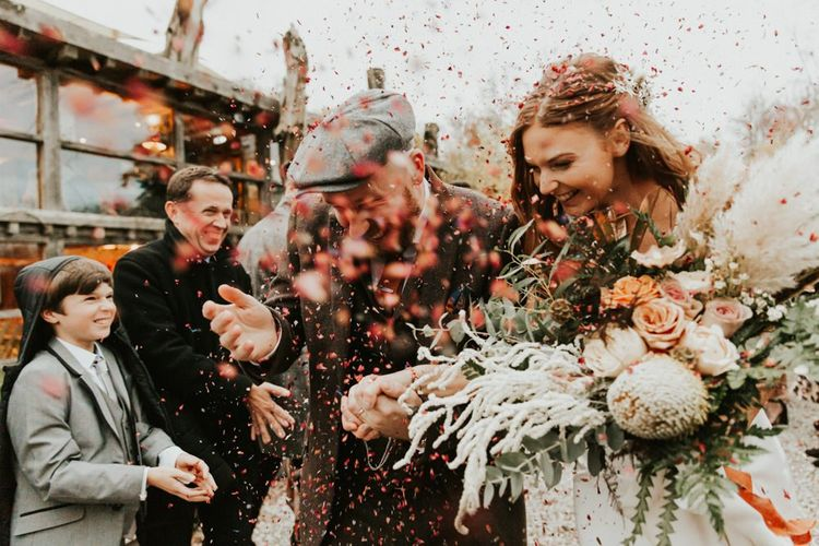 Confetti exit for bride and groom with large bouquet