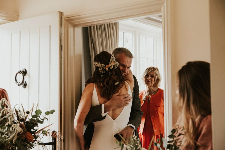 Bride hugs her family before making her way to wedding ceremony with bridal party in bridesmaid jumpsuit