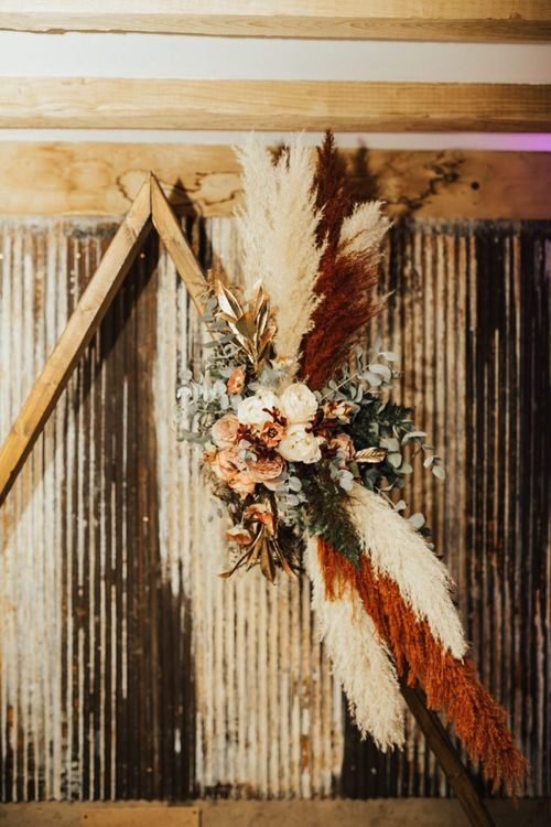 Pampas grass and Autumn flowers with bridesmaid jumpsuit for November wedding