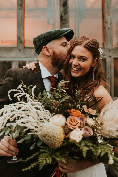Bride and groom at Winter wedding with large bouquet with bridesmaid jumpsuit