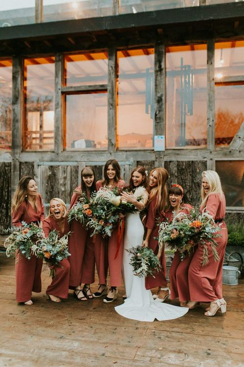 Bridesmaids in bridesmaid jumpsuits in rusty colour