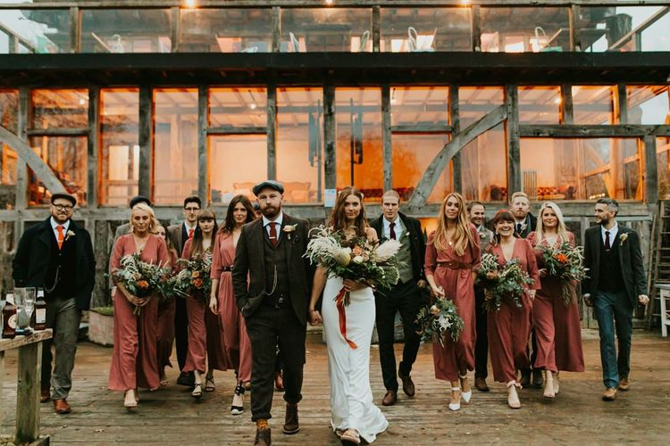 Bridal party in bridesmaid jumpsuits with groomsmen at Kent wedding venue